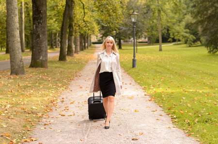 Elegant businesswoman walking through a park pulling an overnight bag along behind her in a concept of travel or business trip