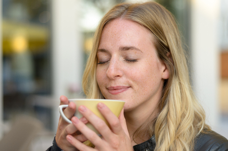 Blissful young woman enjoying a cup of morning coffee savoring the aroma with a happy smile and eyes closed