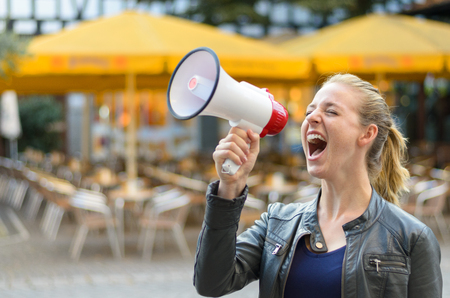 demonstrator: Young woman yelling into a megaphone or bullhorn as she stands outside airing her grievances while participating in a protest Stock Photo