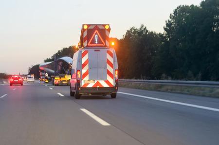Advertencia vehículo de un convoy de trabajo pesado en una carretera conduciendo por detrás de los camiones de transporte con un triángulo de advertencia y luces intermitentes Foto de archivo