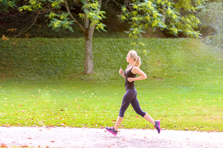 muscle toning: Toned athletic young blond woman enjoying a morning jog through a lush green park in a health and fitness concept Stock Photo