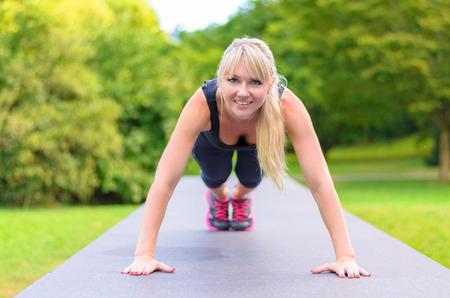 body toning: Fit young blond woman doing exercises in a park performing press-ups on a pathway with looking at the camera with a friendly smile, low angle frontal view in a health and fitness concept Stock Photo