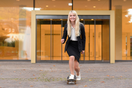 Smiling business or professional woman with her foot on a skateboard in an urban setting standing smiling at the camera, with copy space