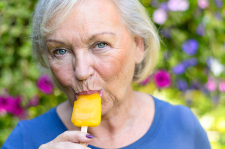 sucks: Attractive blond elderly woman enjoying a refreshing iced orange fruit lolly outdoors on a hot summer day looking at the camera with a quiet smile as she sucks on the sucker