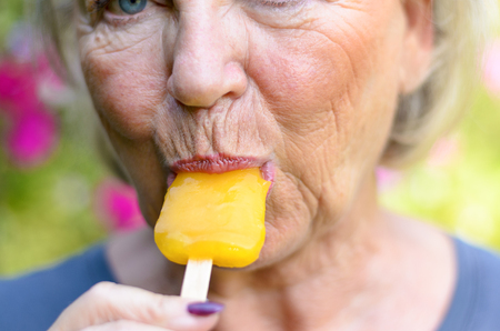 Senior woman sucking on an iced orange lolly outdoors on a summer day cooling off from the heat, close up cropped view on her mouth and lips