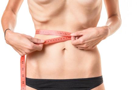 mujeres: mujer joven con peso inferior al que mide su cintura con una cinta métrica con la que sobresalen las costillas y los huesos de la cadera conceptuales de la anorexia o la bulimia, aislado en blanco Foto de archivo