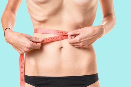 Underweight young woman measuring her waist with a tape measure with protruding ribs and hip bones conceptual of anorexia or bulimia, isolated