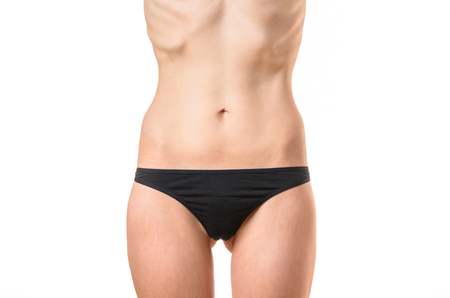 protruding: Very thin young woman with protruding bones and ribs suffering from extreme dieting, starvation or an eating disorder such as bulimia or anorexia isolated on white, close up torso shot