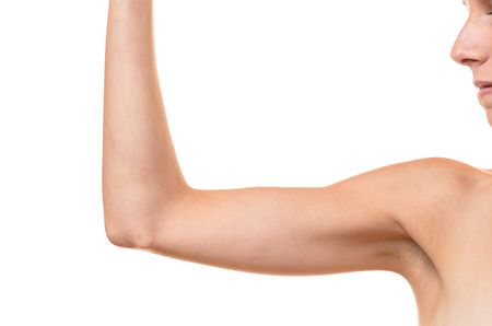 Young blond woman showing flabby arm, effect of aging caused by loss of elasticity and muscle, close-up Stok Fotoğraf - 62861080
