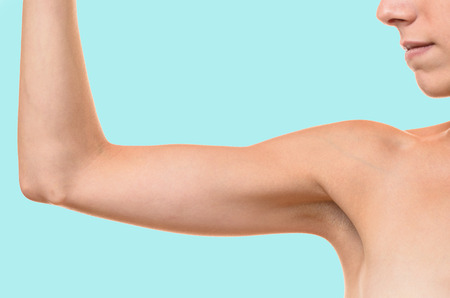 loose skin: Young blond woman showing flabby arm, effect of aging caused by loss of elasticity and muscle, close-up