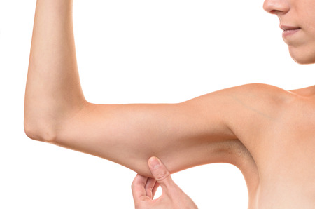 loose skin: Young woman displaying the loose skin or flab due to ageing on her upper arm pinching it between her fingers, close up view