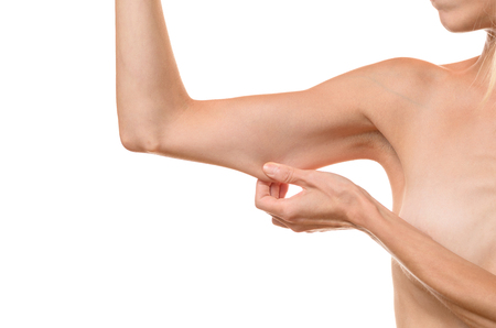 ageing: Young woman displaying the loose skin or flab due to ageing on her upper arm pinching it between her fingers, close up view