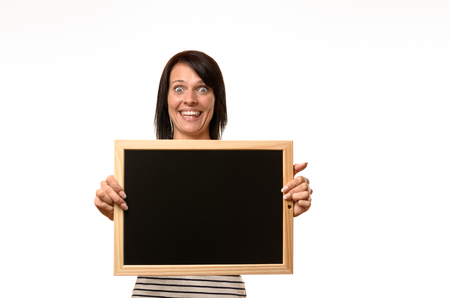 empty of people: Happy laughing young woman with a blank school slate or chalkboard in her hands with copy space for your text or advertisement isolated on white