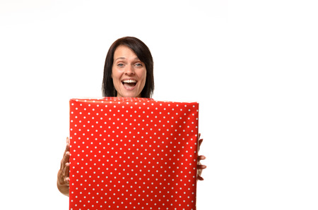 giftwrapped: Happy overjoyed woman holding a large red gift box in her hands looking over the top with a beaming smile for a Valentines, Christmas, anniversary or birthday concept isolated on white