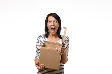 astounded: Front view of single surprised woman in striped shirt and brown hair holding an open cardboard box