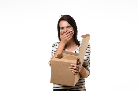 giggling: Front view of single surprised woman in striped shirt and brown hair laughing or shocked while holding open cardboard box
