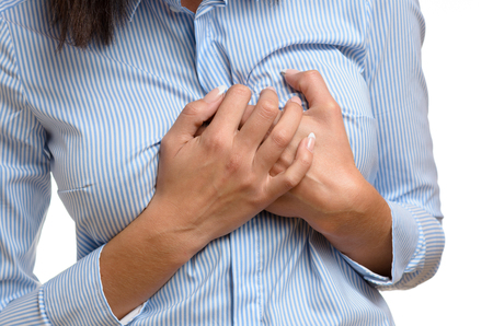 Woman clutching her breast in pain as she suffers the preliminary symptoms of a heart attack or myocardial infarct, close up body view isolated on white Фото со стока