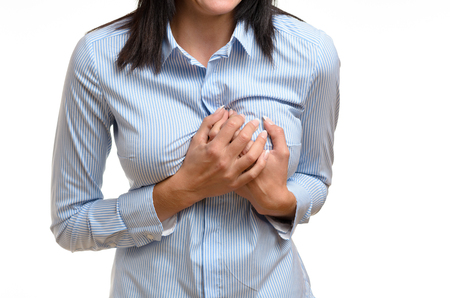 Woman clutching her breast in pain as she suffers the preliminary symptoms of a heart attack or myocardial infarct, close up body view isolated on white Foto de archivo