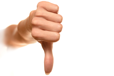 front view of female hand showing thumbs down sign against white background Stock Photo