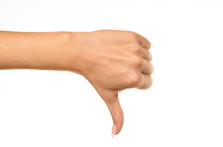 Side view of female hand showing thumbs down sign against white background