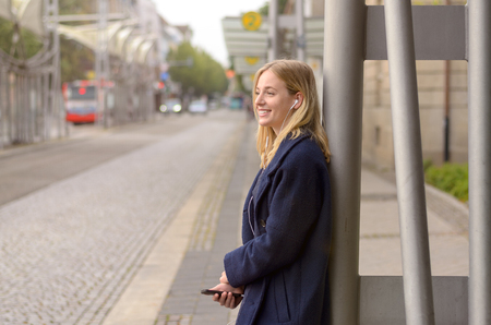 buss: Smiling young woman standing outside the buss stop waiting for her bus with her mobile phone in her hand as she listens to music, side view with copy space Stock Photo