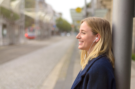 buss: Smiling young woman standing outside the buss stop waiting for her bus while she listens to music, side view with copy space