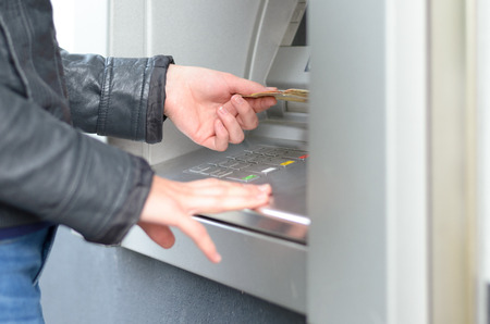 dispense: Young woman making a banking withdrawal at an outdoor ATM standing waiting for the machine to dispense the cash or banknotes, close up side view of her hands