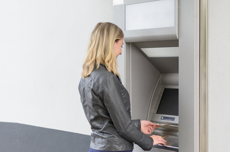dispense: Young woman withdrawing money at an ATM standing with her back to the camera waiting for the machine to dispense the banknotes