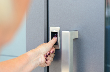 Woman using scanner to read her thumb print to gain electronic access to a door, close up over the shoulder view