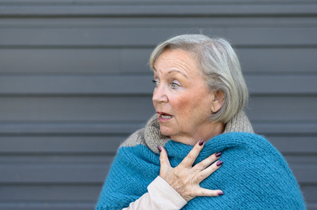 agape: Startled elderly woman clasping her chest in astonishment looking off to the side with a shocked expression and mouth open, grey wall background with copy space