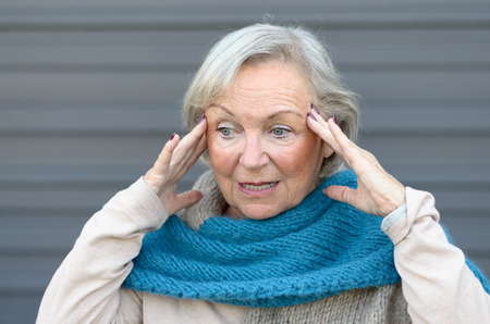 Confus et senior lady ahuri tenant ses mains à ses tempes comme elle regarde de côté, conceptuel de l'apparition de la démence ou la maladie d'Alzheimer