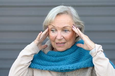 Verward en verbijsterd senior dame houdt haar handen tegen haar slapen als ze kijkt opzij, conceptuele van het ontstaan van dementie of de ziekte van Alzheimer