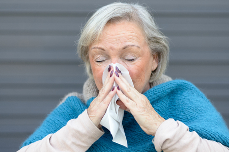 hayfever: Elderly woman with seasonal influenza, a cold, rhinitis or allergic hayfever blowing her nose on a handkerchief in front of a grey wall Stock Photo