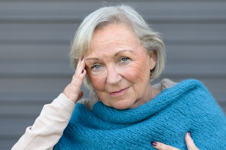 throbbing: Elderly elegant woman with a headache holding her hand to her temple while looking at the camera with eyes dulled by pain