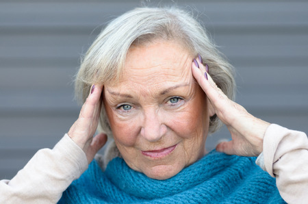 throbbing: Attractive stylish elderly blue-eyed woman standing in front of a grey wall with her hands to her temples looming at the camera with a quiet smile Stock Photo
