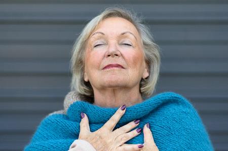 Attraente donna di alto livello assaporando il momento in piedi con gli occhi chiusi e la testa piegata all'indietro, con un'espressione serena mentre si stringe il petto con le mani Archivio Fotografico