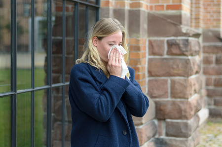 hayfever: Sick young woman blowing her nose on a tissue or handkerchief as she stands outdoors in town, conceptual of a seasonal flu epidemic or allergic rhinitis Stock Photo