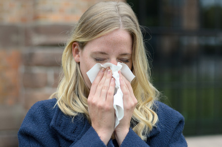 Young woman suffering from a seasonal cold and flu blowing her nose on a handkerchief as she stands outdoors in town in a healthcare and medical concept Фото со стока