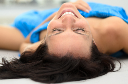 rejuvenated: Cute young woman grinning as she relaxes in bed under blue bedclothes, view from the top of her head with focus to her face Stock Photo