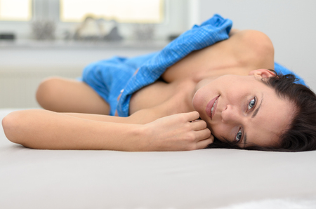 rejuvenated: Pretty young woman enjoying a relaxing day lying on her bed covered by a blue sheet looking up at the camera with a smile, low angle view from the top of her head Stock Photo
