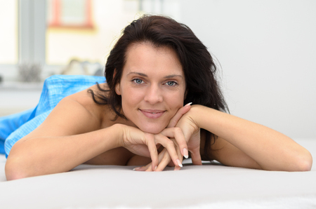 rejuvenated: Attractive friendly woman relaxing on her bed lying on her stomach looking at the camera with a quiet friendly smile as she rests her chin on her hands