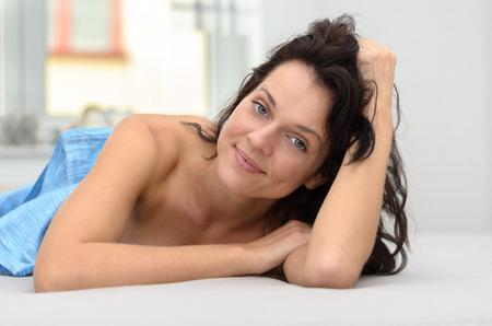 Gorgeous charismatic young woman with long brown hair relaxing in bed lying on her stomach grinning happily at the camera Stock Photo