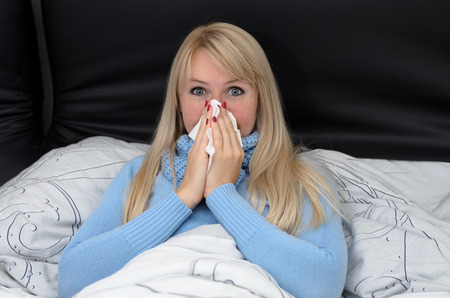 hayfever: Sick woman blowing her nose in bed sitting propped up against the pillows suffering from a seasonal cold , hayfever or influenza Stock Photo