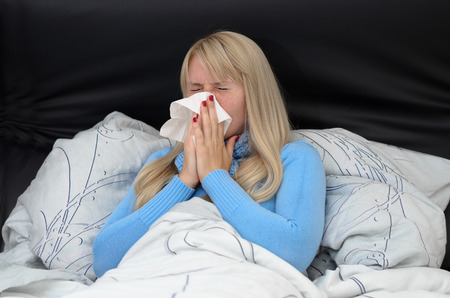 Sick woman suffering from seasonal hayfever or flu sitting propped up in her bed blowing her nose on a handkerchief with her eyes closed