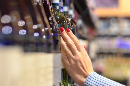 Woman choosing a bottle of wine off the shelf in a supermarket with a close up oblique angle view down the row of bottles to focus on her hand