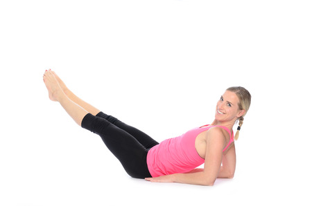 Fit smiling woman looking over shoulder while doing abdominal exercises with alternating leg extensions over white background