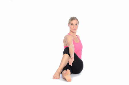 Beautiful athletic woman with calm expression twisting herself for a stretch over isolated white background