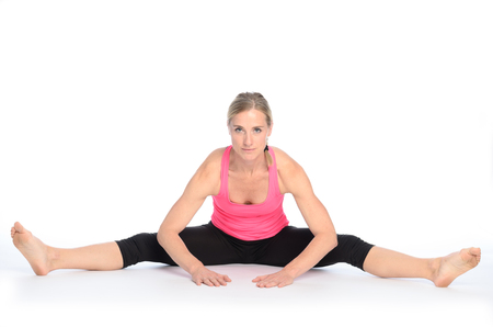 Young woman performing a straddle split stretch with legs far apart over white background