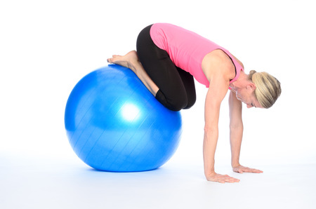 Sporty barefoot young woman working out with a pilates ball balancing on her legs and hands with controlling and strengthening her muscles isolated on white Stock Photo