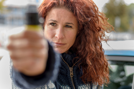 automobile door: Close up view of pepper spray in hand of serious adult woman in curly red hair standing outside near automobile door